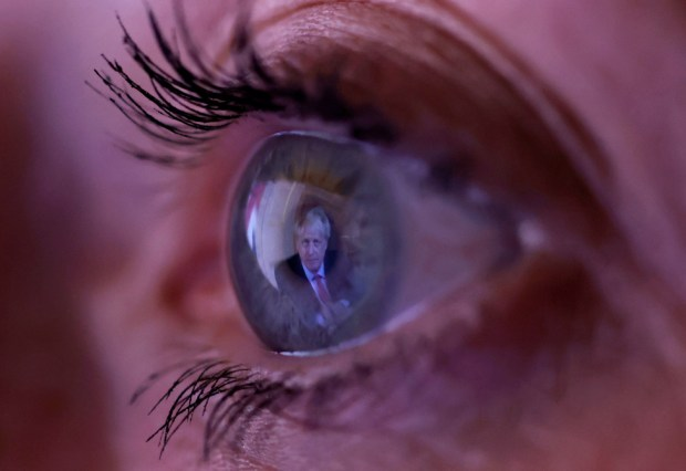 A close up of a woman's eye with the image of Boris Johnson reflected in her iris