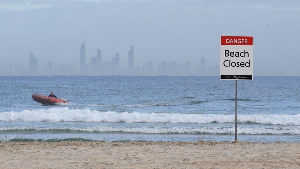 Lifeguards patrol waters off a closed Gold Coast beach after a fatal shark attack