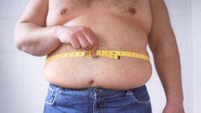 Hombre con sobrepeso midiéndose la cintura