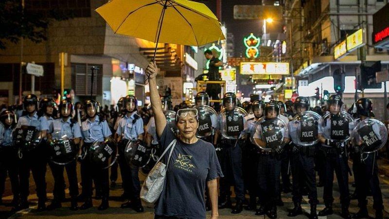 Una activista prodemocracia sostiene una sombrilla amarilla frente a una fila de policías en Hong Kong en 2014.