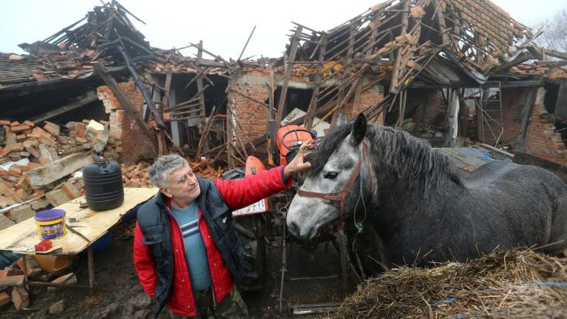 Farmer Tomislav Suknaic touches his horse in front of his damaged household in Majske Poljan village