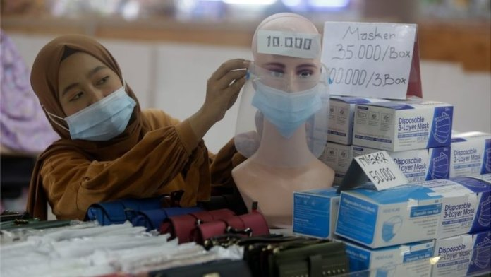 A vendor arranges a mask attached to a mannequin at a shopping mall in Jakarta, Indonesia, 04 January 2021.