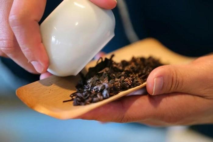 Tea master Xingcai Zhang poured House Goddess Tea leaves onto a bamboo holder.
