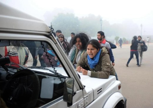Demonstrators attempt to stop a police car during a protest calling for better safety for women in NewDelhi on Dec. 23. Several thousand students attended the protest, where they were met with water cannons and tear gas by the police.