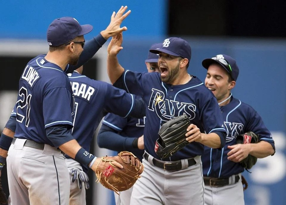 James Loney (left), Matt Joyce (center), and Sam Fuld celebrate the Rays' victory.