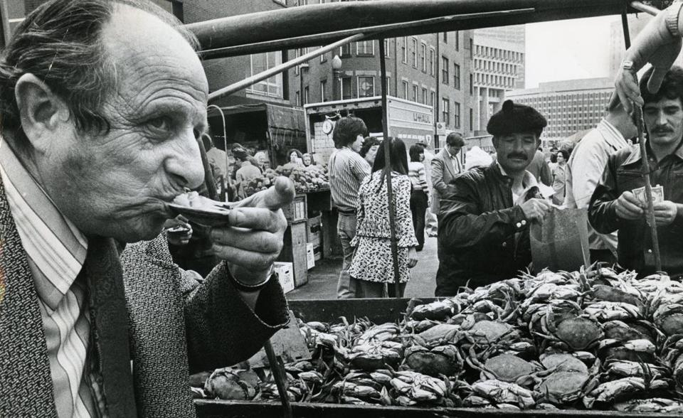 May 18 1973 / fromthearchive / Globe Staff photo by Charles Dixon / While one of his customers put an oyster to the taste test, vendor Joe Judge (wearing beret) sold some boiled crabs to another on a busy afternoon in Boston's Faneuil Hall market district.<br /><br />