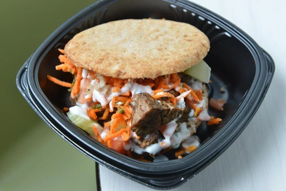 Beef pita pocket with raw vegetables and yogurt-mint sauce.