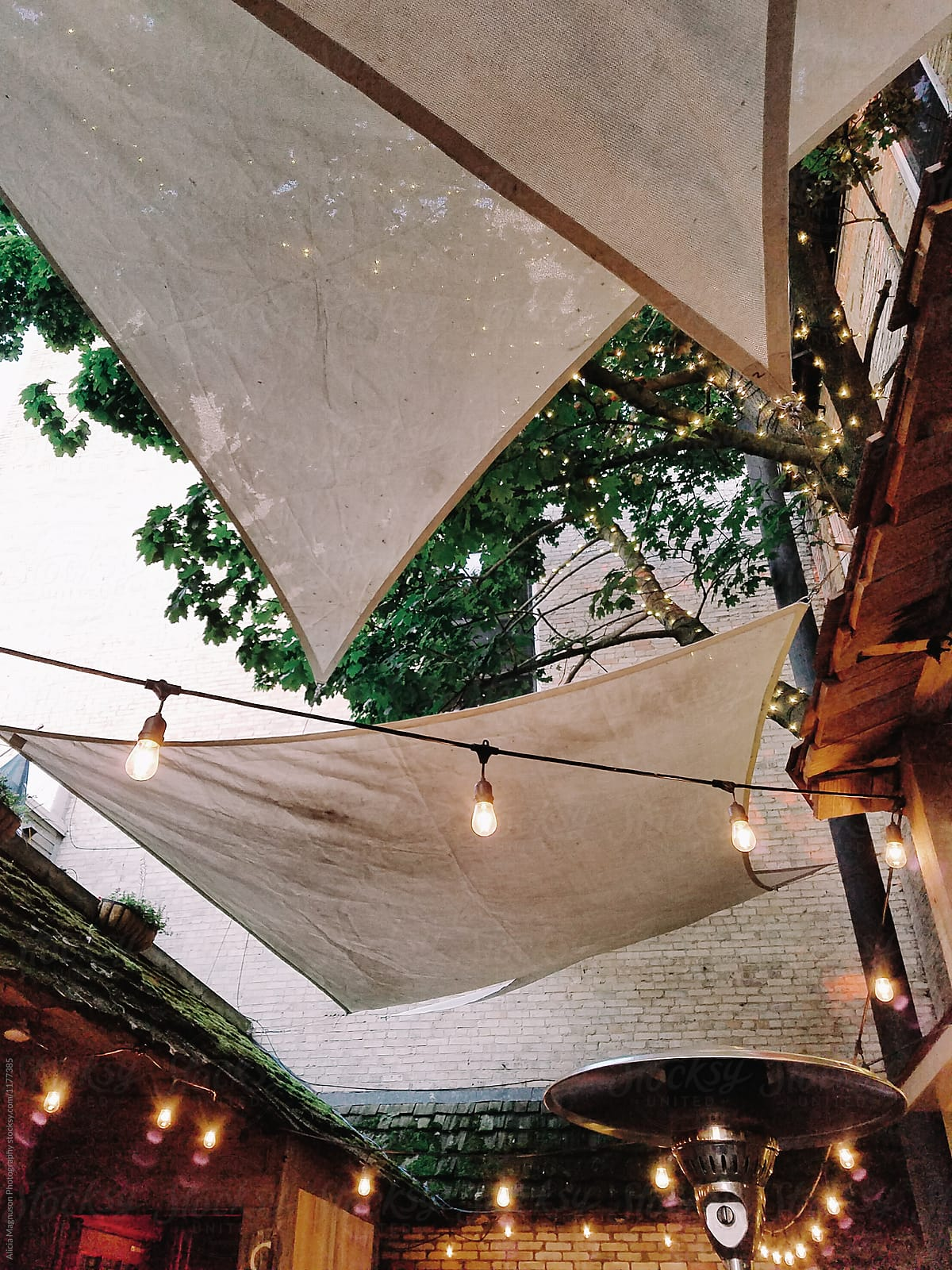 shade tarps and cafe lights at outdoor bistro by alicia magnuson photography for stocksy united