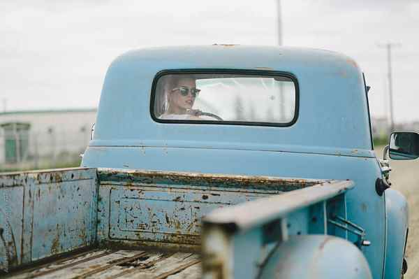 Blond girl driving an old pickup truck by Ania Boniecka