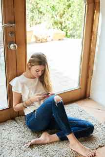 Barefoot Woman In Ripped Jeans Browsing Cell Phone Rug