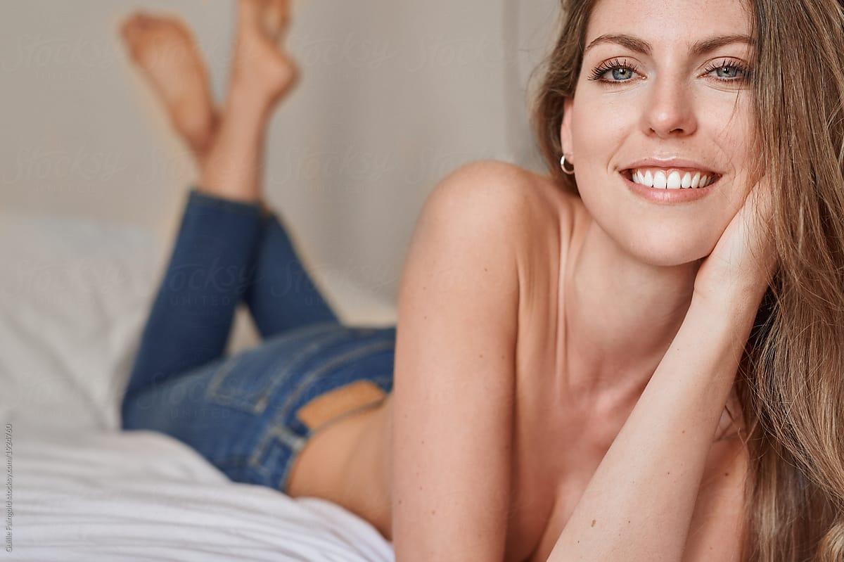 beautiful topless woman in denim lying
