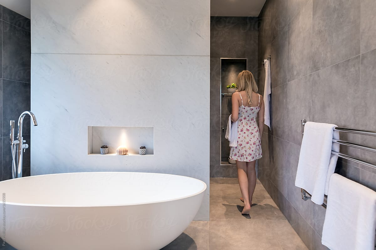 Modern Bathroom Stock Photo Modern Bathroom With Oval White Freestanding Bath Woman Walking To The Shower Behind