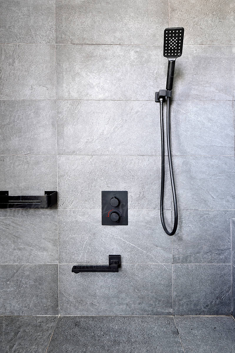 luxury shower with granite tiles and black shower fixtures by carli teteris for stocksy united