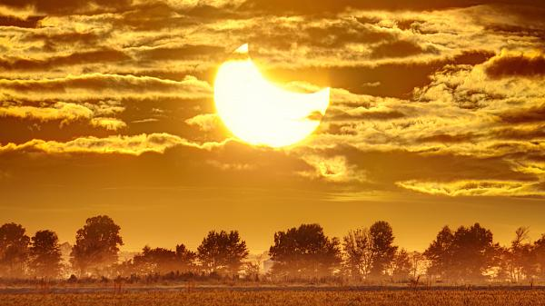 Hình ảnh có các cánh đồng ở tiền cảnh và Mặt trời hình lưỡi liềm với Mặt trăng ở phía trước. Bầu trời nhiều mây trong nền.