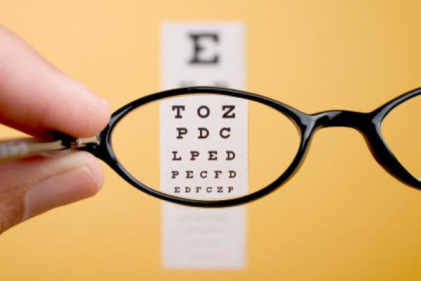 Looking through eyeglasses at an eye exam chart.