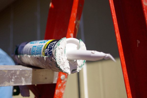 Tube of caulk resting on a ladder