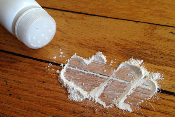 Fixing a squeaky wood floor by sprinkling talc