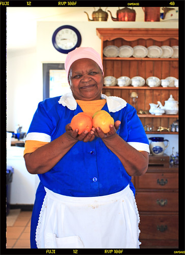 AN AFRICAN MAID  A cheerful maid offers some juicy