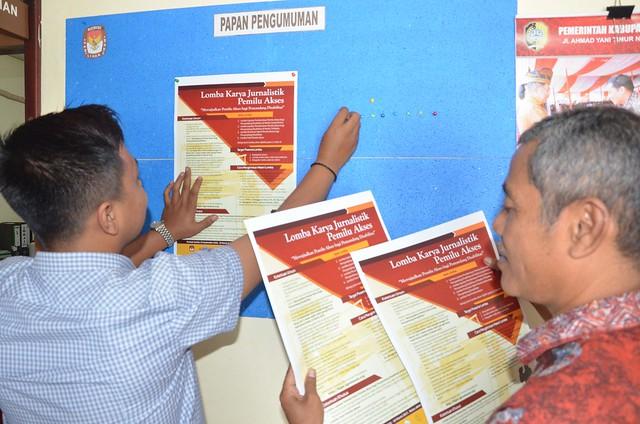 Staf sekretariat KPU Kabupaten Tulungagung tengah menempelkan poster lomba karya jurnalistik(27/1)