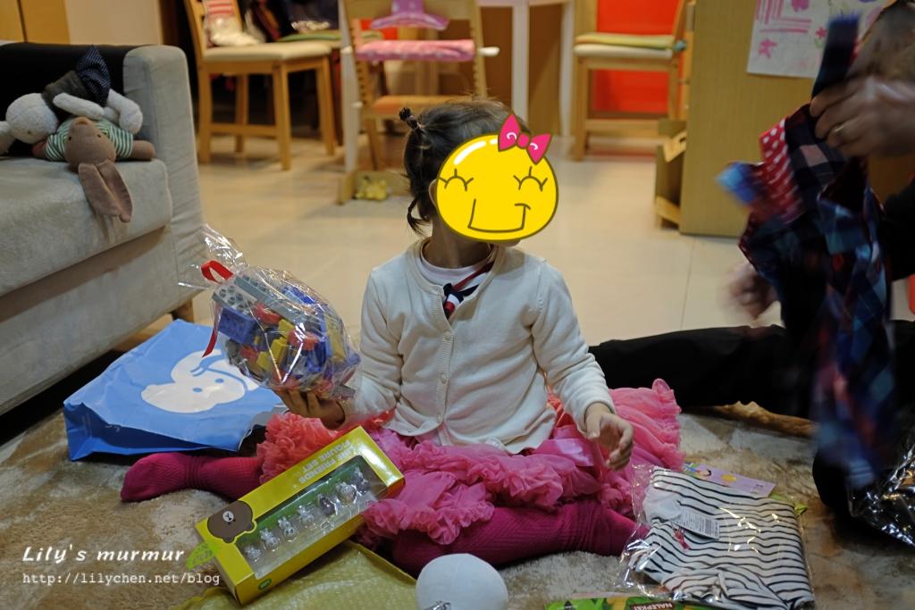 正在興奮拆禮物的小妮,外婆跟媽媽在旁邊幫忙檢視禮物。
