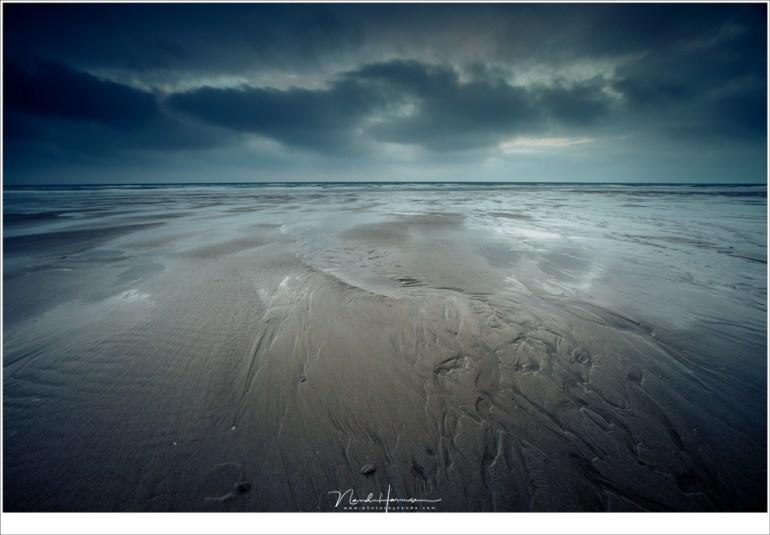 Langzaam verschijnt er kleur in de hemel, maar veel is het niet. In de verte is de zee, die sporen in het zand achtergelaten heeft toen het zich terug trok (16mm | ISO100 | f/11 | t=1,6sec | grijsverloopfilter)