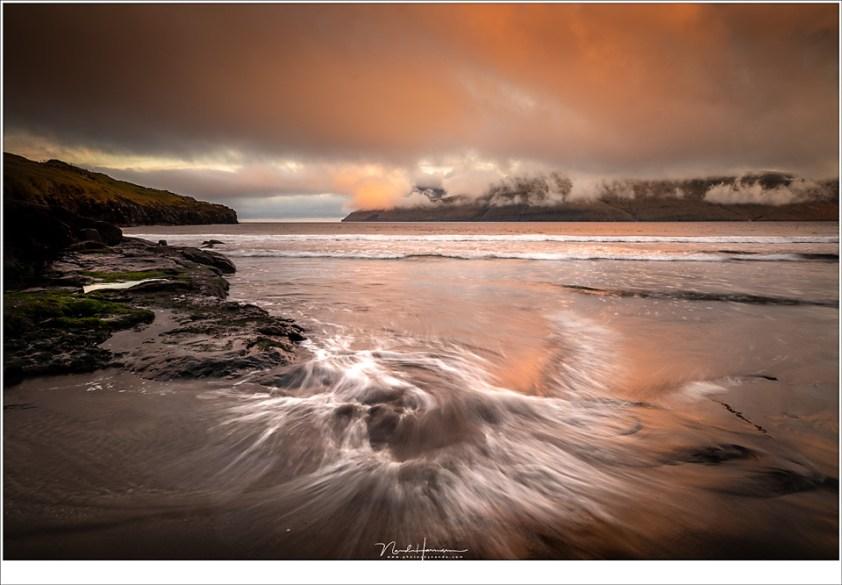 Faeröer eilanden - deel 3, Het was grijs bewolkt op het strand van Leynar, tot er geheel onverwacht tegen zonsondergang een oranje kleur in de wolken verschijnt. (23mm   ISO200   f/11   0,5sec   grijsverloopfilter)