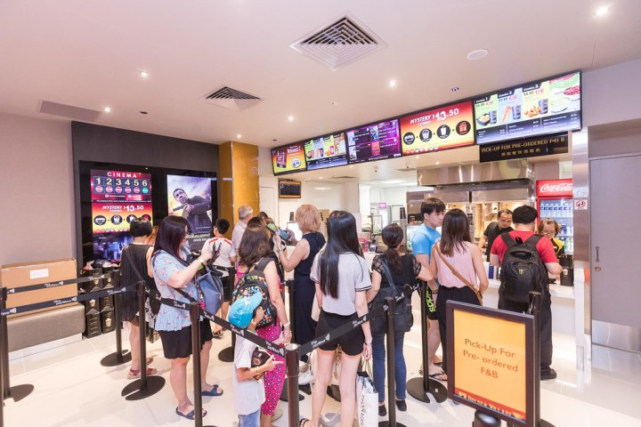 The first walk-in customers on GV Bedok's opening day queuing at the box office/candy stand. Photo: Golden Village