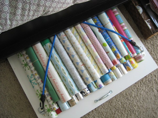 Under bed wrapping paper storage Bungee cords used to