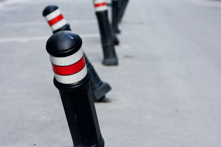 A row of black parking poles with yellow accents on top