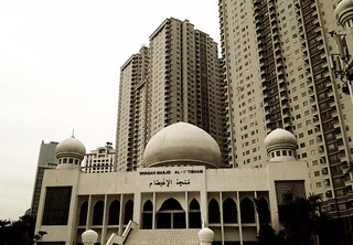 mosque in front of tall apartment buildings in jakarta