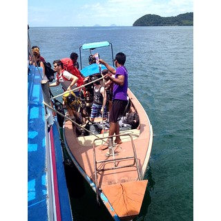 embarking on longtail boat in adamant sea in thailand