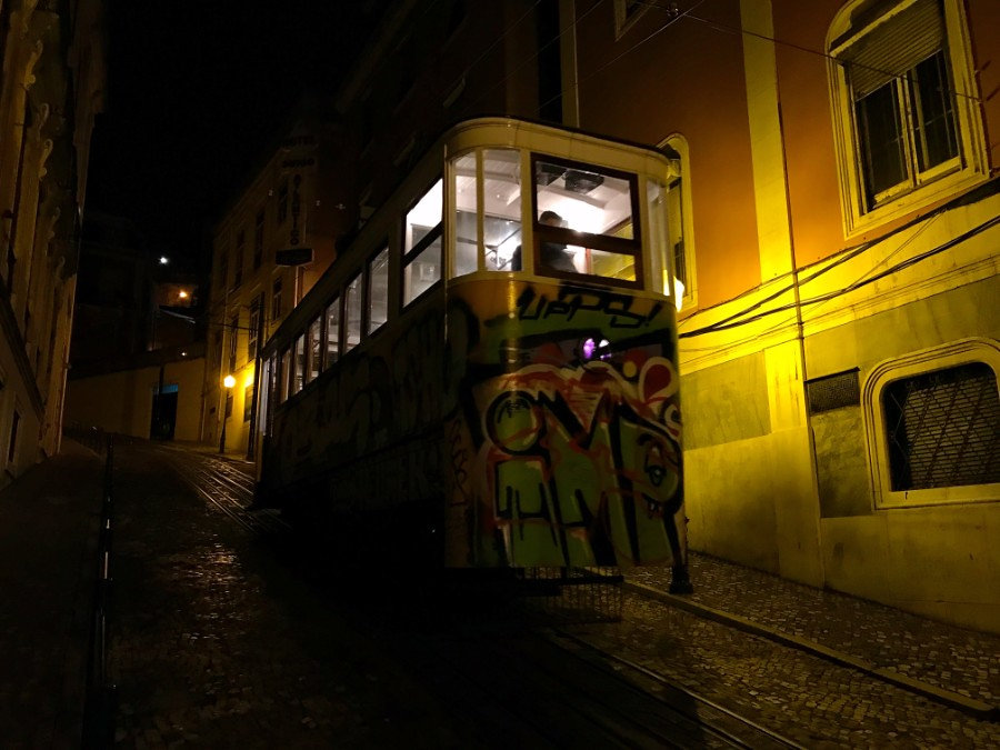 tram with graffiti going up steep road in lisbon
