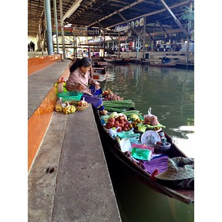 woman selling vegetables from boat in damnoek saduak floating market