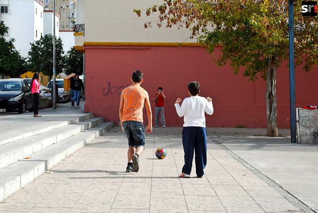 Tres niños juegan a la pelota en una de las plazas de Tres Barrios
