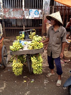 man selling bananas on a bicycle in a market in makassar