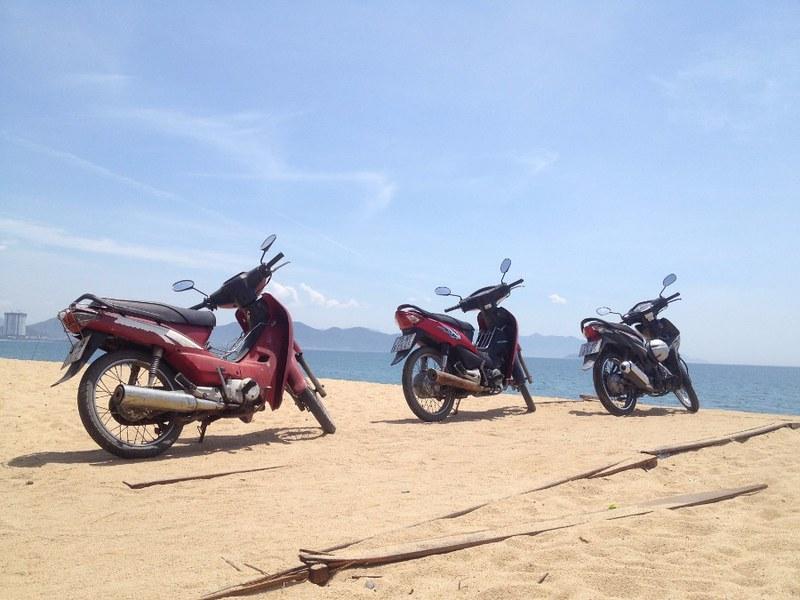 three underbone motorbikes parked on beach in nha trang, vietnam