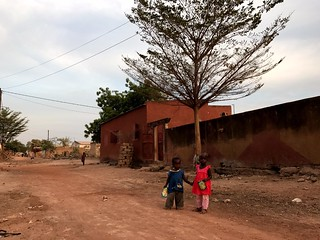 two little kids holding each other's hand in a street in tambacounda, senegal