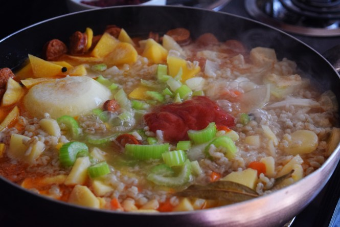 Add tomato paste and celery to Barley Stew with Root Vegetables and Sausage
