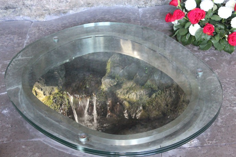 Through this opening on the floor of the Grotto, one can view the healing waters of Lourdes