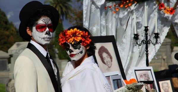 お墓の前で骸骨メイクをしたカップル