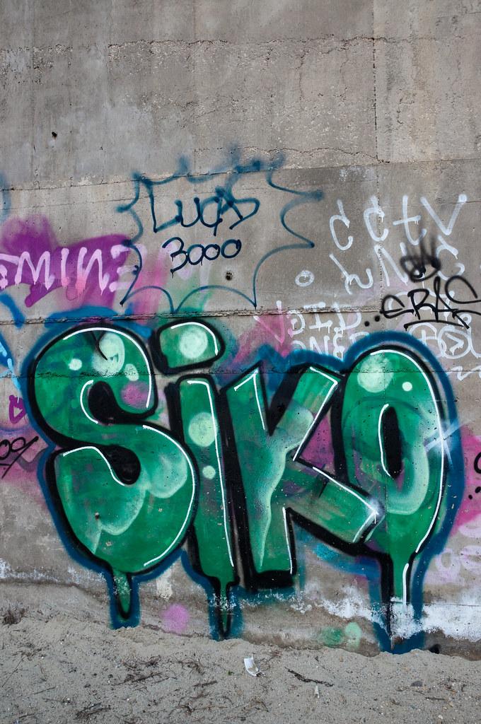 Large green Siko graffiti on concrete wall  Large green
