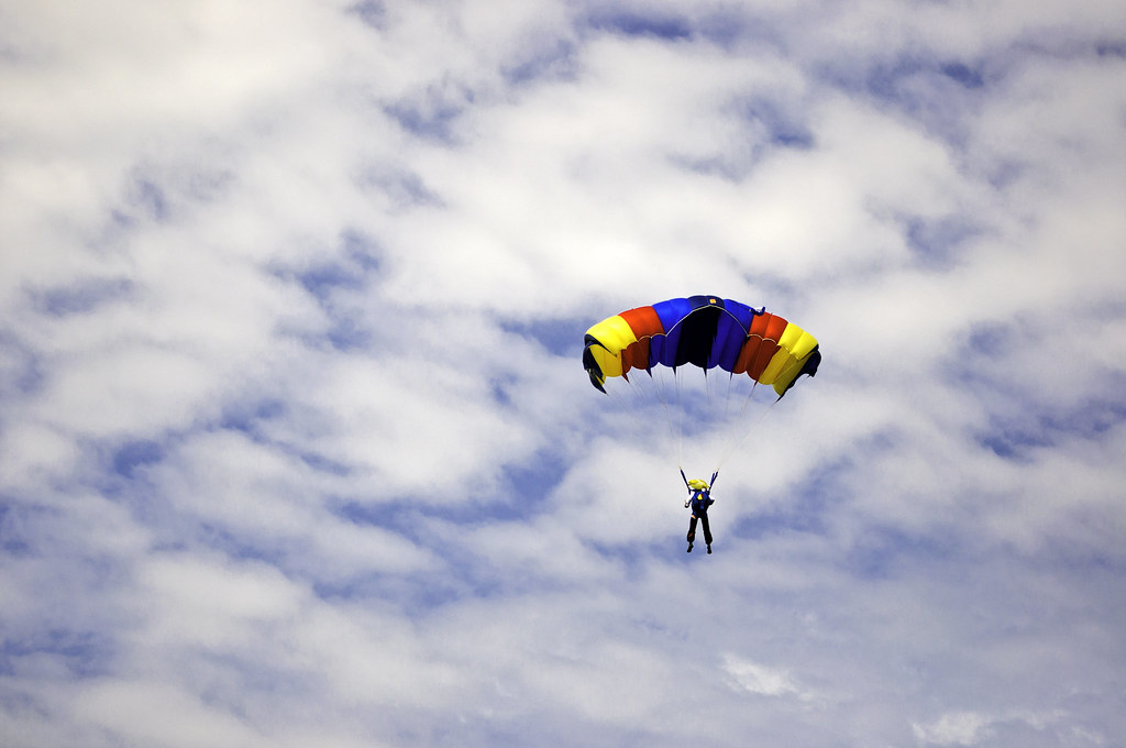 Parachute jumper against cloudy sky  Man jumping with a