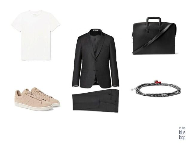 Traje para hombre negro combinado con sneakers, camiseta blanca, pulsera y maletín
