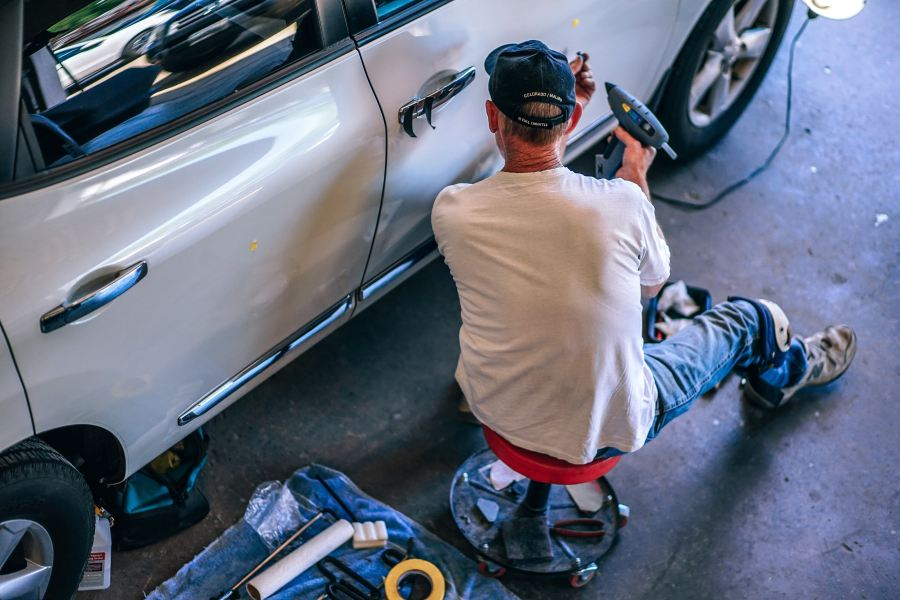 A car mechanic working on a vehicle\'s exterior.