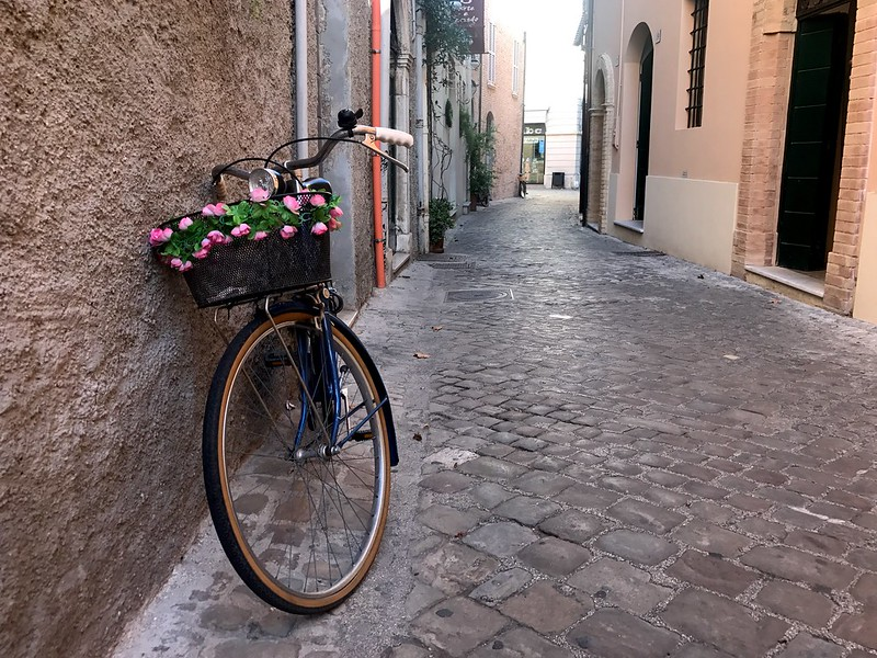 bicycle with pink flower basket in the streets of senigallia