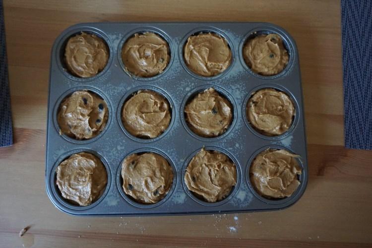 Gluten free blueberry pumpkin muffins batter poured into a muffin tin