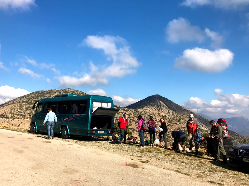 green bus stopped by mountain dirt road and hikers getting ready to climb mount artemision