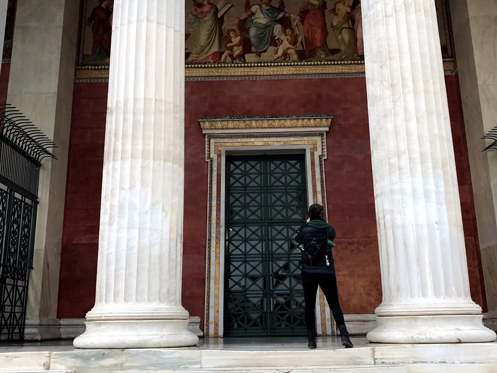 girl photographing the entrance of athens university
