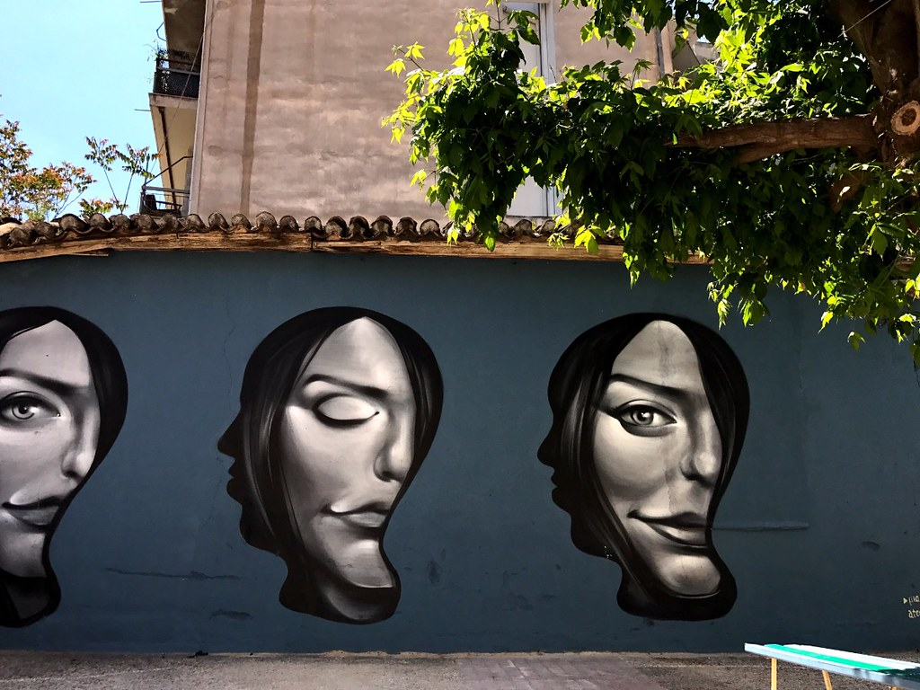 graffiti of three distorted women faces on with closed eye the other with open on a house wall in athens