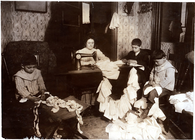 Romana making dresses for Campbell Kid Dolls in a dirty tenement room